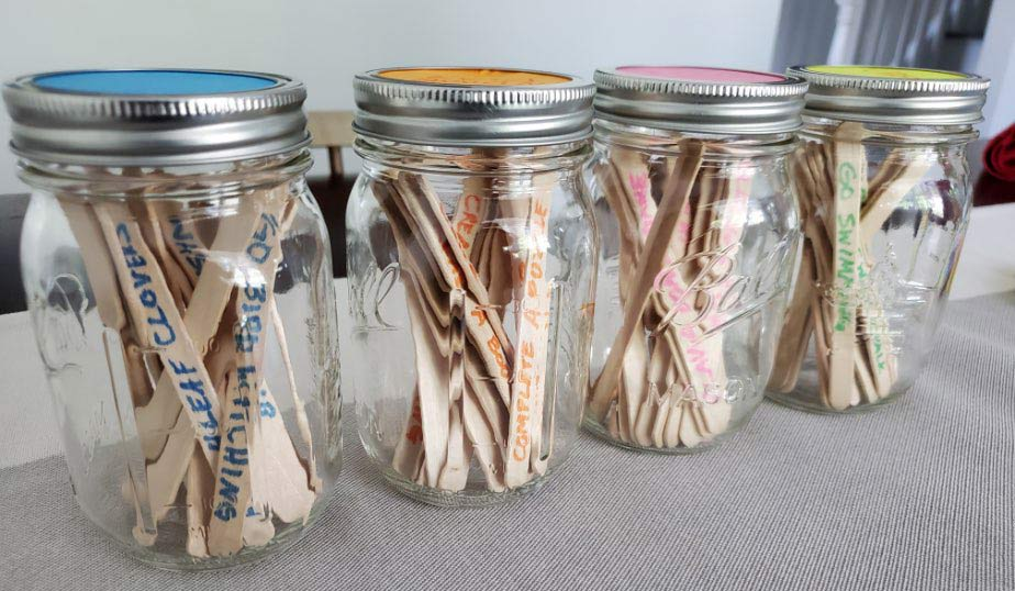 completed activities jar with popsicle sticks inside mason jars