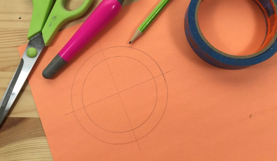 orange construction paper with circles drawn in pencil