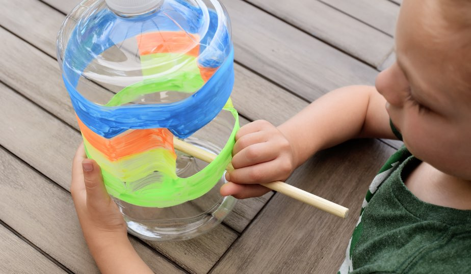 young child sticking dowel through painted diy bird feeder, an activity idea for kids