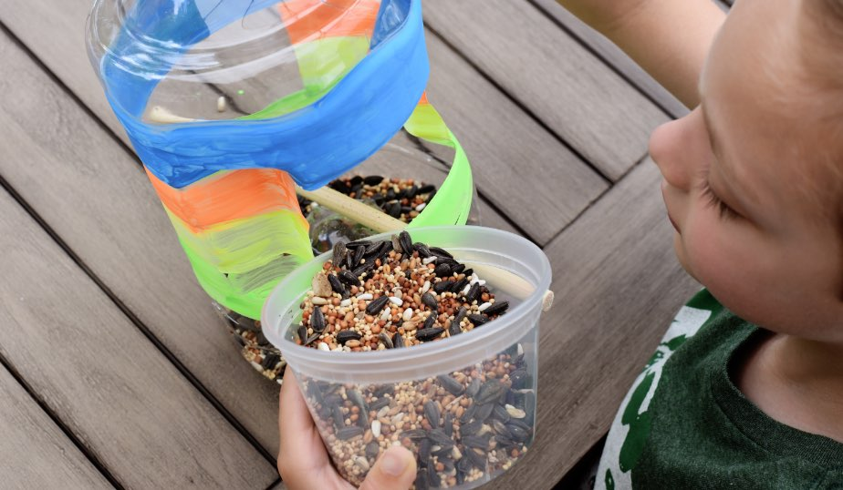 child pouring bird seed into the diy bird feeder, an activity idea for kids