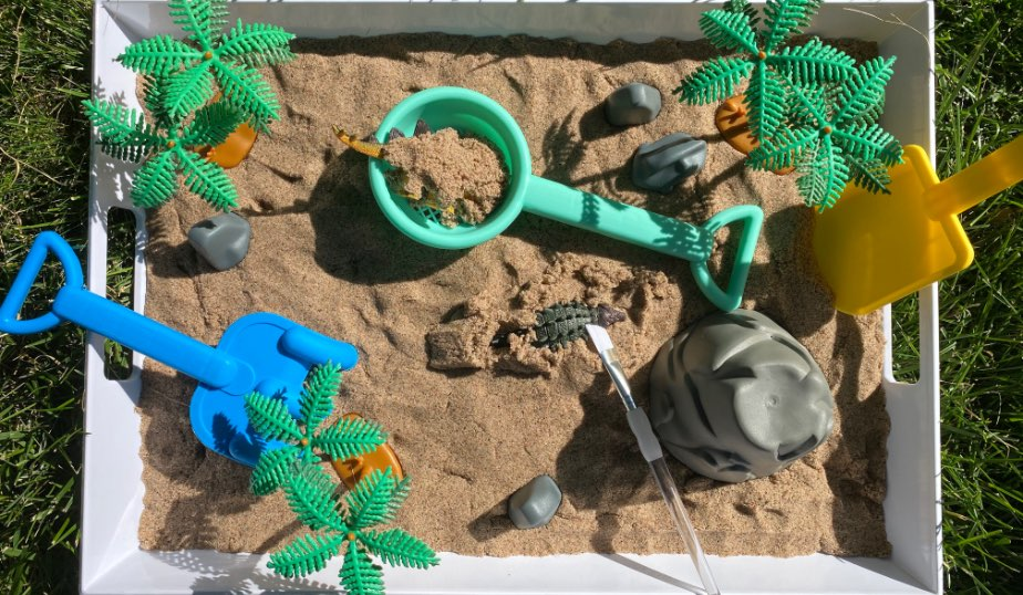 sand and beach toys for excavating the dino figures from the dino discovery diy for kids