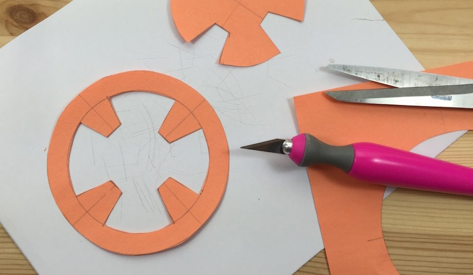 orange construction paper and craft knife supplies