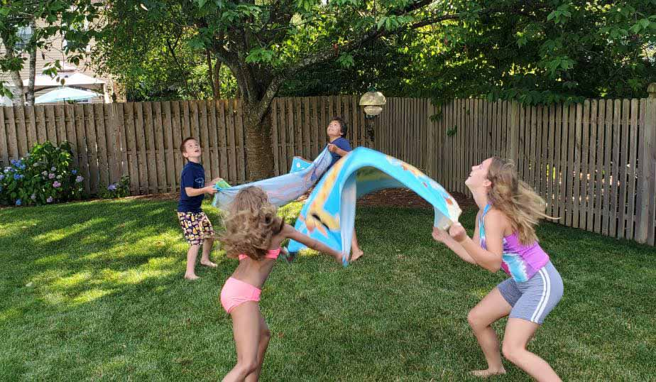 young children tossing Bunch O Balloon water balloons in backyard game for kids