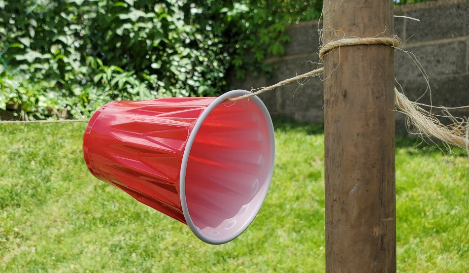 red plastic cup secured to a post with string