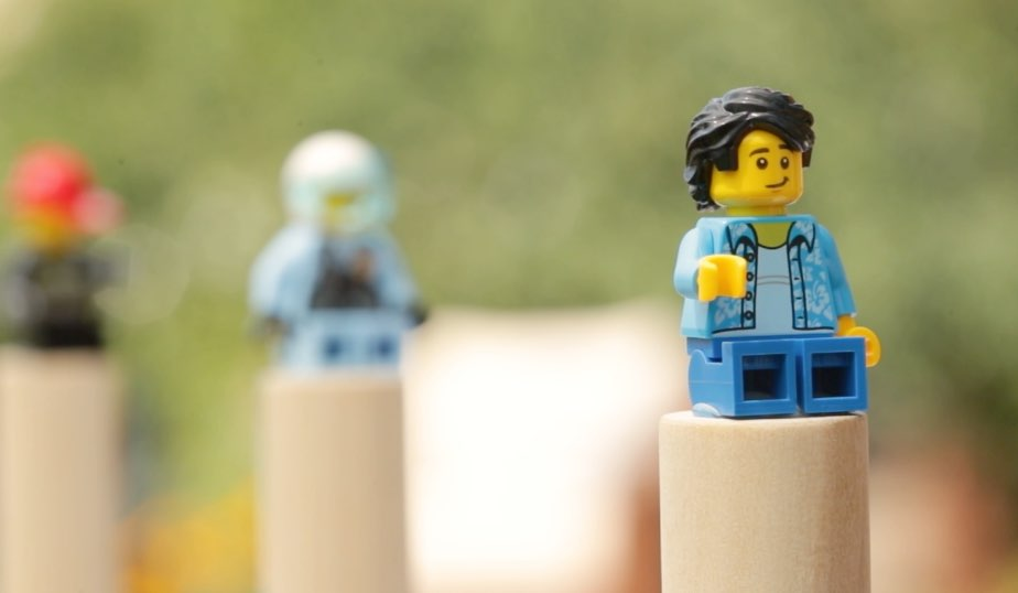 hot glue secures LEGO minifigures to dowel