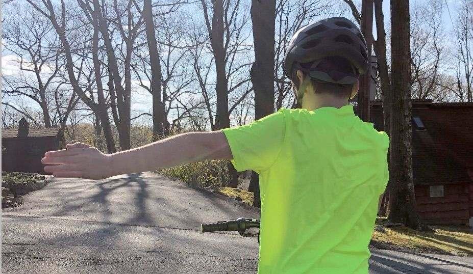 boy uses left hand signal on his bike